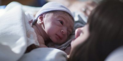A newborn in a blue cap baby rests on his mother's chest and looks into her eyes.